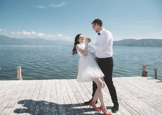 Nevěsta v krátkých šatech tančící na mole se ženichem